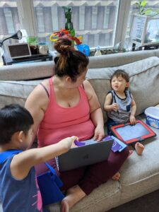 Adult female with two kids sitting on a couch