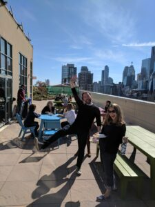 A group of people gathered outside talking on a rooftop overlooking a city. There is a blue sky and it is sunny. The people are sitting at picnic tables and there is people standing and waving.
